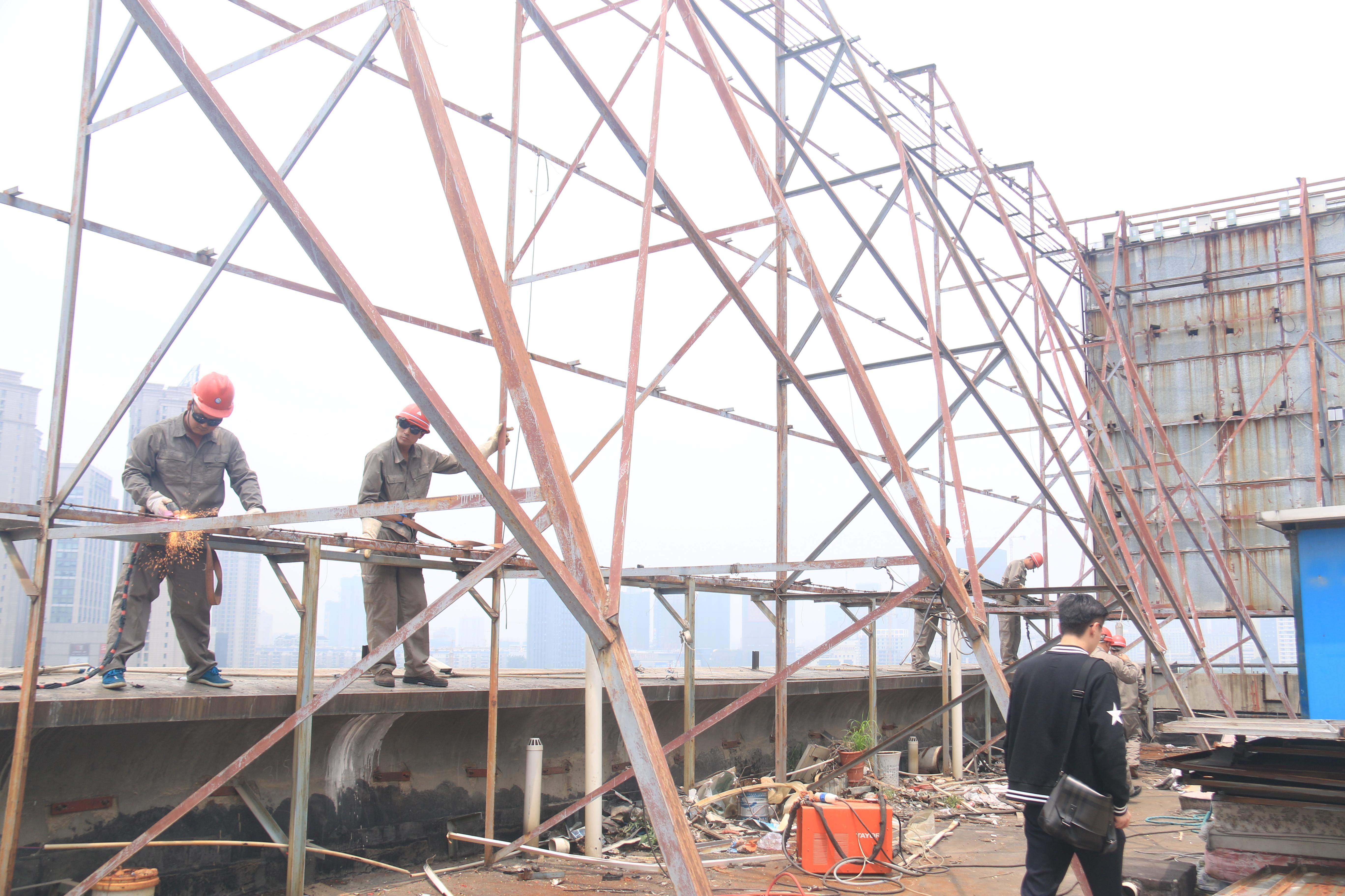 工人们正拿着氧焊机切割固定在广告牌上的铁架,一辆巨大的吊车缓缓将