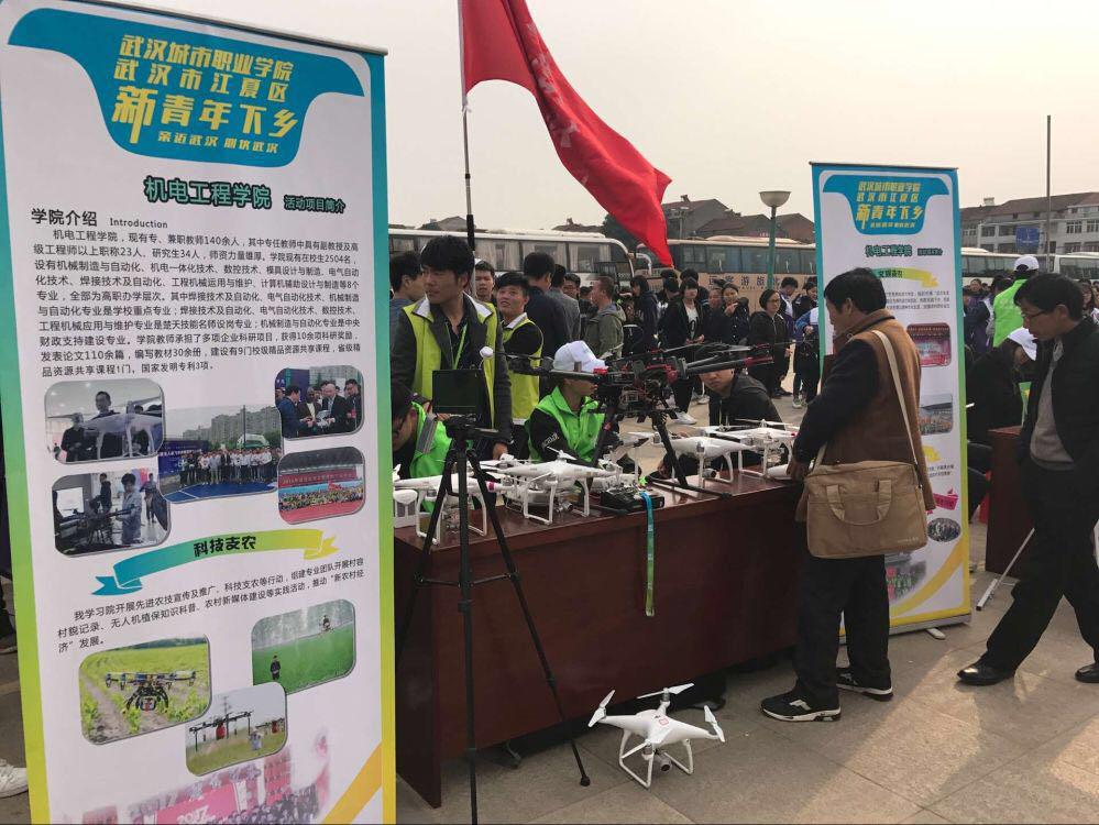 学院机电学院无人机协会的学生教村民用无人机监测作物长势,喷洒
